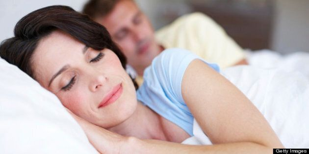 A mature couple sleeping in their bedroom at