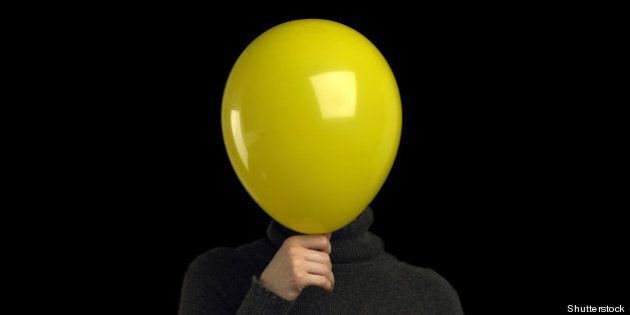 a yellow balloon over a persons