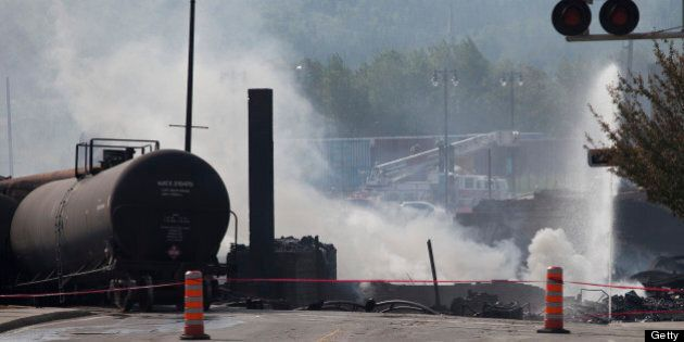 Wreckage continues to burn on July 7, 2013 after a freight train loaded with oil derailed July 6 in Lac-Megantic...