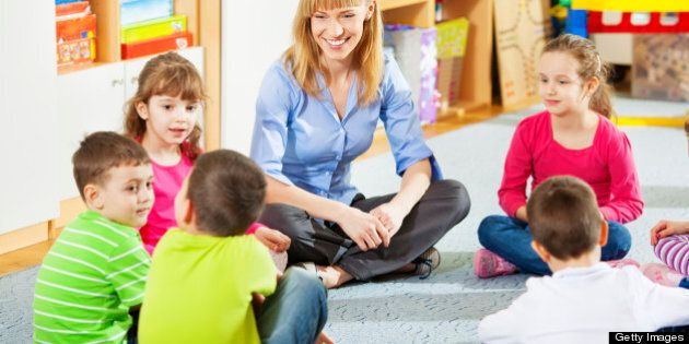 Preschool: Young smiling teacher discussing with group of children. Learning and having fun. Selective...