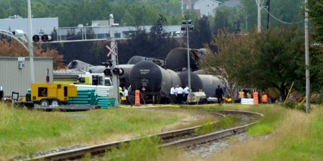 Investigators work at the train derailment site July 9, 2013 in Lac-megantic, Quebec, Canada. The death toll from the massive explosion caused by a runaway oil tanker train that derailed July 6 and flattened part of the small Canadian town has risen to 13, a coroner said Monday, and dozens more remain missing. Confirmation of eight further deaths in Lac-Megantic, in Quebec province, came as environmental officials warned that around 100,000 liters of oil spilled in the disaster was headed for the Saint Lawrence seaway. PHOTO STEEVE DUGUAY-AFP (Photo credit should read STEEVE DUGUAY/AFP/Getty Images)