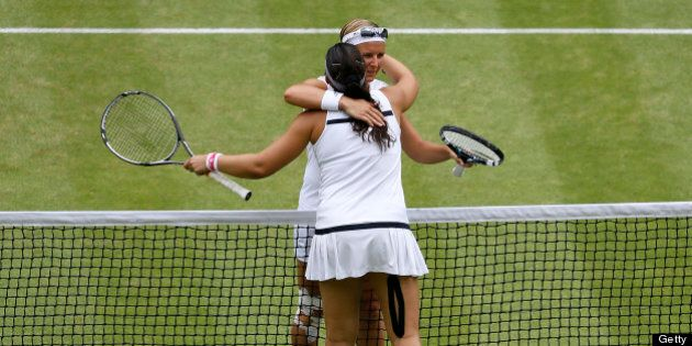 Belgium's Kirsten Flipkens (back) embraces France's Marion Bartoli (front) at the net after Bartoli's...