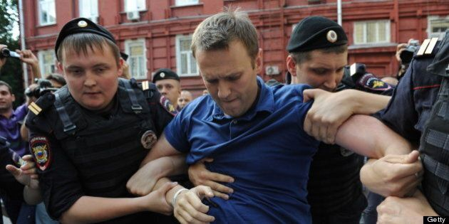 Police officers detain Russia's top opposition figure Alexei Navalny (C) after his visit the city's election...
