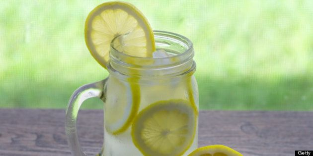Refreshing glass of ice cold lemonade with a slice of lemon on the side of the glass.