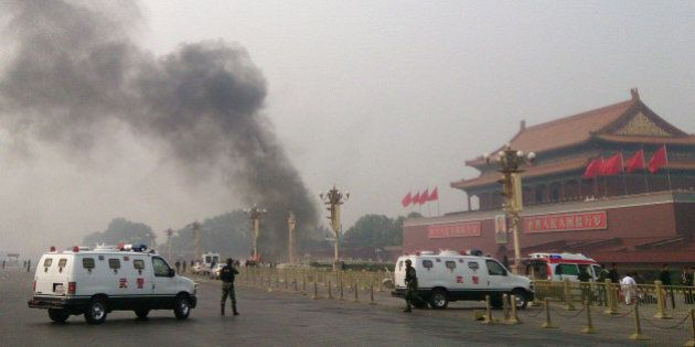 Police cars block off the roads leading into Tiananmen Square as smoke rises into the air after a vehicle...