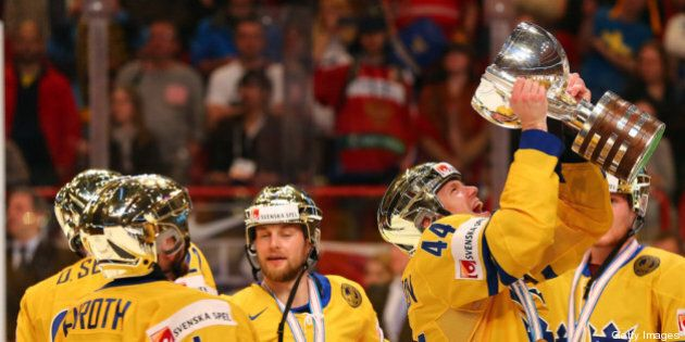 STOCKHOLM, SWEDEN - MAY 19: Nicklas Danielsson (#44) of Sweden lifts the trophy after winning the IIHF...