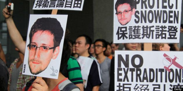 Protesters hold placards outside government headquarters during a rally in support of Edward Snowden,...