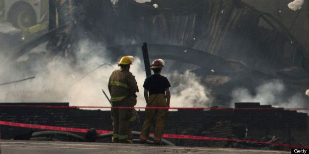 LAC-MEGANTIC QC - JULY 7: Firemen looked at the smouldering remains of a derailed train. Three people have now been declared dead and dozens remain missing after a train derailment caused a massive explosion in the quaint Quebec town of Lac-MÈgantic. (Lucas Oleniuk/Toronto Star via Getty Images)