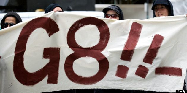 Protesters hold up a banner against the G8 Summit outside the BP head office in central London on June...