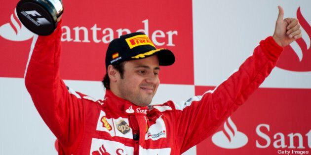 Ferrari's Brazilian driver Felipe Massa celebrates on the podium at the Circuit de Catalunya in Montmelo...