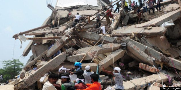 Bangladeshi volunteers and rescue workers are pictured at the scene after an eight-storey building collapsed...