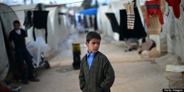An internally displaced Syrian boy stands near tents in the Maiber al-Salam refugee camp along the Turkish...
