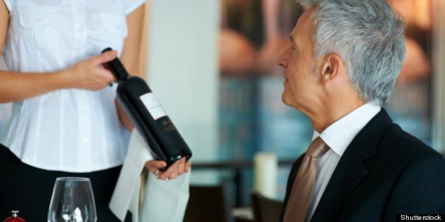 Waitress showing a well dressed man the wine of his selection at the
