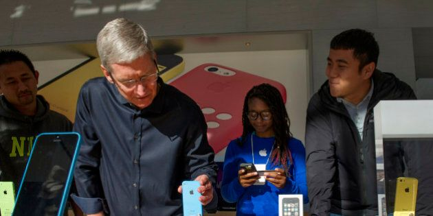 Tim Cook, chief executive officer of Apple Inc., second left, adjusts an Apple Inc. iPhone 5c displayed...