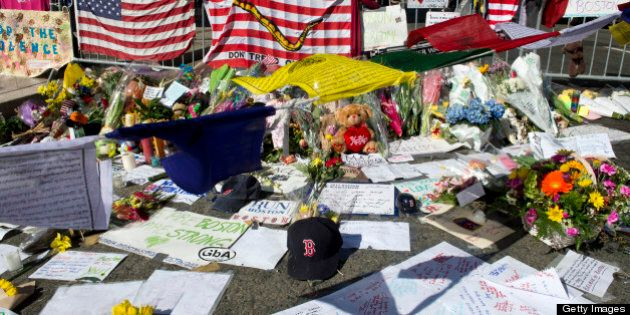 A Boston Red Sox cap is part of a makeshift memorial on the Boston Marathon route April 18, 2013 in Boston,...