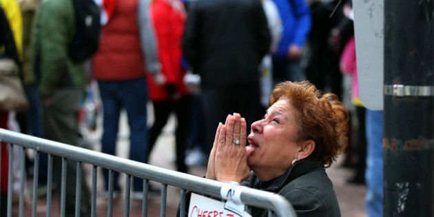 BOSTON - APRIL 15: A woman kneels and prays at the scene of the first explosion on Boylston Street near...
