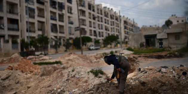 A Syrian rebel patrols the area in the Sheikh Maqsud district of the northern Syrian city of Aleppo,...