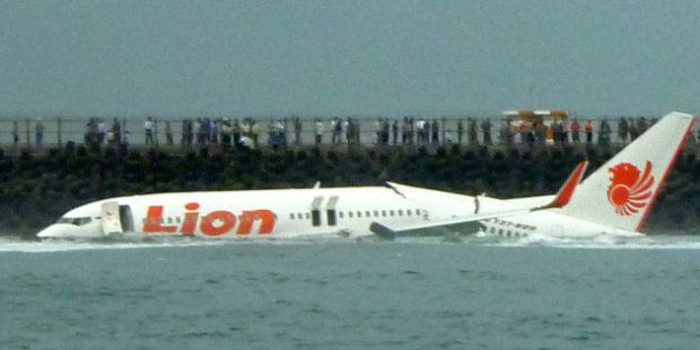 A Lion Air Boeing 737 lies submerged in the water after skidding off the runaway during landing at Bali's...