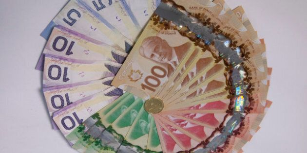 Canadian dollar bills are arranged with a coin for a photograph in Toronto, Ontario, Canada, on Tuesday, Feb. 26, 2013. Canada?s dollar traded at almost the weakest level in eight months versus its U.S. counterpart amid political turmoil in Europe and before data this week that may show the nation?s economy stalled. Photographer: Pawel Dwulit/Bloomberg via Getty Images