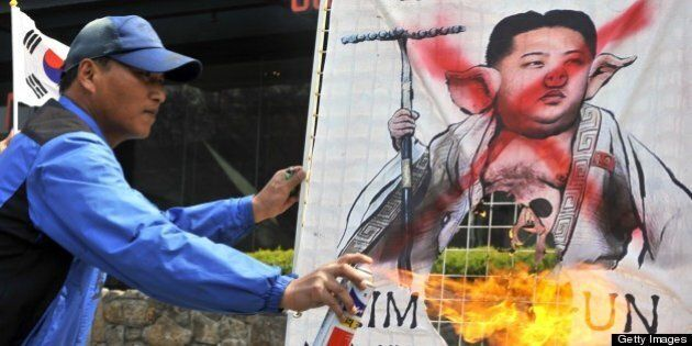 A South Korean activist burns a placard showing a caricature of North Korean leader Kim Jong-Un during...