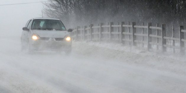 Vehicles drive through drifting snow on the A6 road near the town of Buxton in north-west England, on...