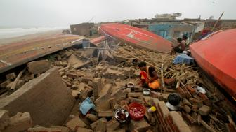 A woman cooks a meal outdoors after her house was damaged by Cyclone Fani in the Penthakata fishing village of Puri, in the eastern Indian state of Orissa, Saturday, May 4, 2019. A mammoth preparation exercise that included the evacuation of more than 1 million people appears to have spared India a devastating death toll from one of the biggest storms in decades, though the full extent of the damage was yet to be known, officials said Saturday. (AP Photo)