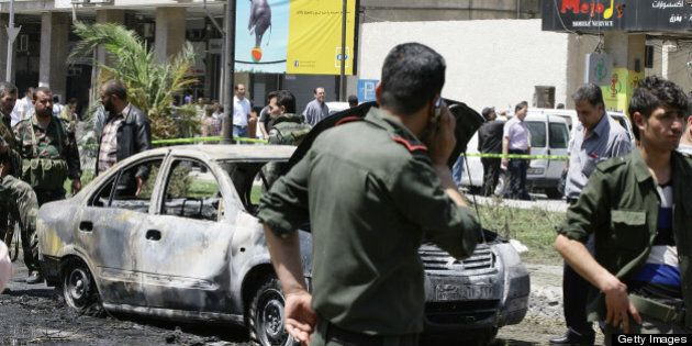 Syrian government security officers close of the area following a blast in the Marjeh district of Damascus,...