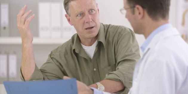 Doctor talking to mature male patient