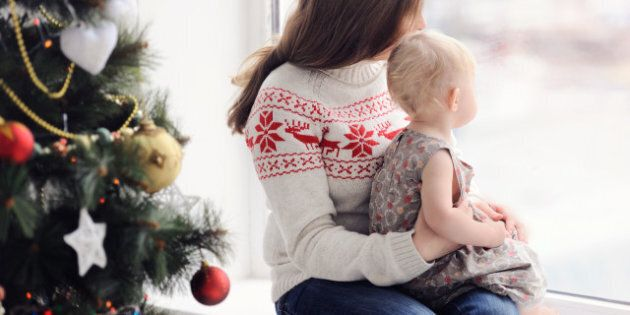 Mother with baby sitting by the window. Christmas decorations. On Christmas, waiting for a miracle. A...