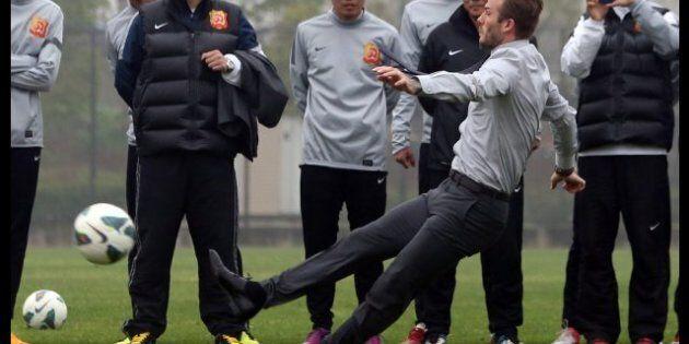 David Beckham en Chine essaie de tirer un coup franc en costume et finit par terre