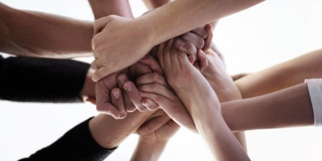 A low angle cropped shot of a group of people holding hands together during a support group