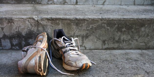 A pair of old used running shoes on cement