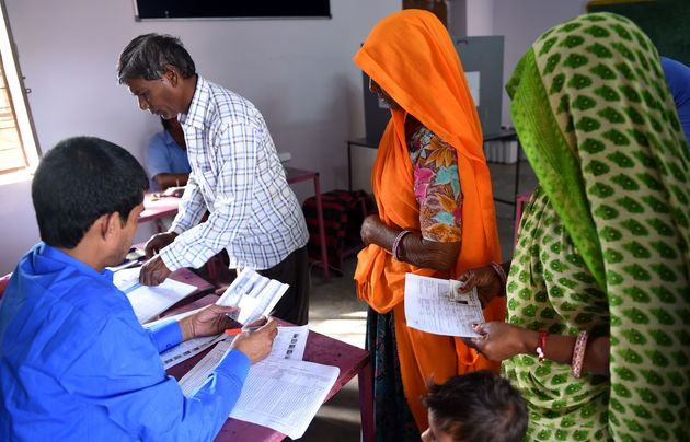 Voters check their name before casting their vote during general election in village Kapoorawala, in...