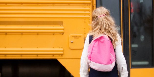 Elementary girl with a back pack heading toward the school