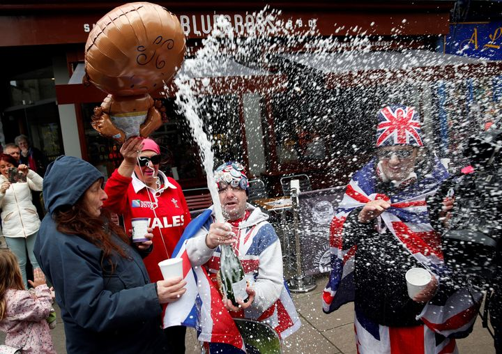 Royal super fans John Loughery (C) pops the cork on a bottle of Champagne, as they stand near Windsor Castle on Monday, follo