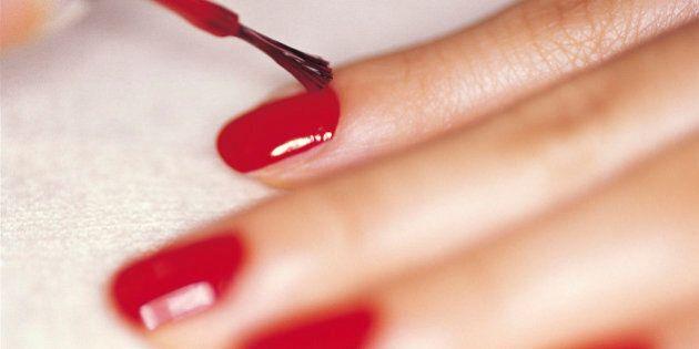 Close-up studio shot of woman applying nail