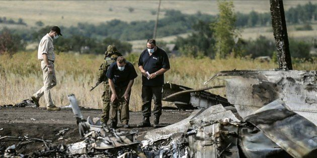 Investigators work at a the crash site of the Malaysia Airlines Flight MH17 near the village of Hrabove...