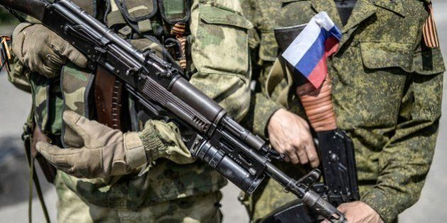 A pro-Russia separatist with a Russian national flag attached on his uniform, stands next a comrade, at a checkpoint near the front line in the northern outskirts of city of Donetsk, on July 22, 2014. Terrified civilians fled as intense clashes yesterday between Ukrainian government troops and pro-Russian rebels left at least four people dead on the outskirts of the insurgent bastion of Donetsk. A military spokesman said yesterday government troops were battling back control of the districts around the airport and had broken through the rebel cordon to reach their comrades inside.  AFP PHOTO/ BULENT KILIC        (Photo credit should read BULENT KILIC/AFP/Getty Images)