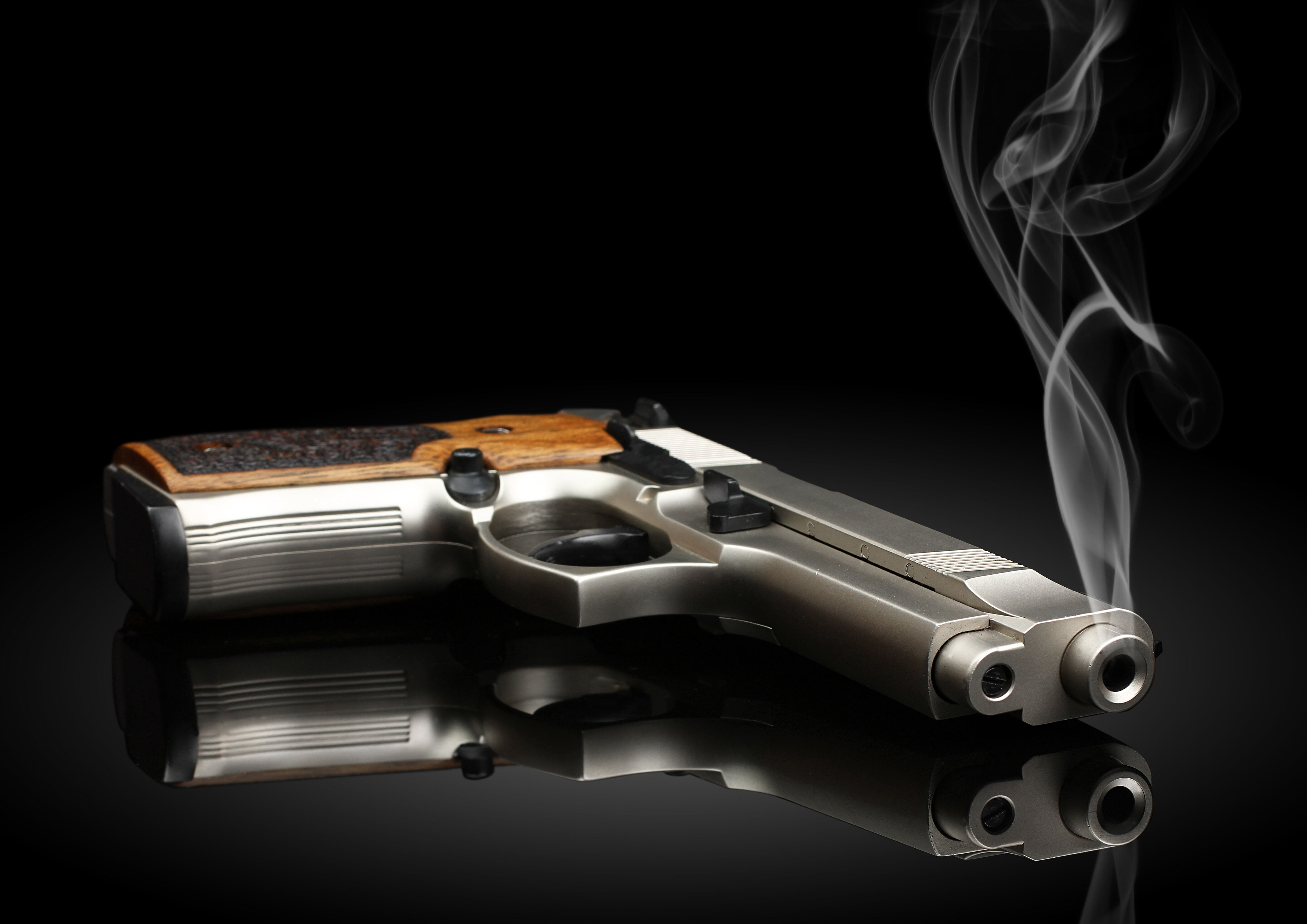 Chromed handgun on black background with smoke