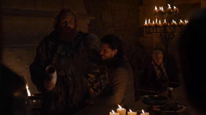 The cup can be seen at the bottom right of the photo, on the table in front of Dany.