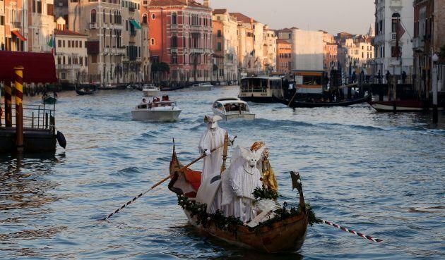 Des personnes masquées circulent en gondole à Venise pendant le célèbre Carnaval, une des périodes fortes...
