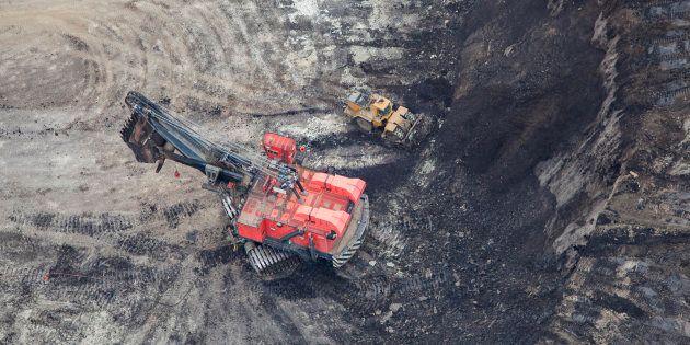 Une grande pelle mécanique extrait les sables bitumineux d'une mine à ciel ouvert en Alberta, près de...