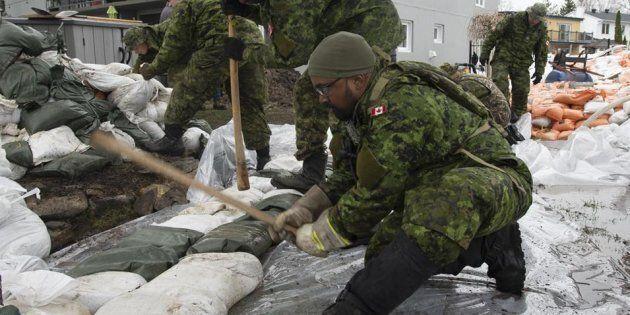 Des membres de l'armée canadienne compactent des sacs de sable pour protéger des maisons le long de la...