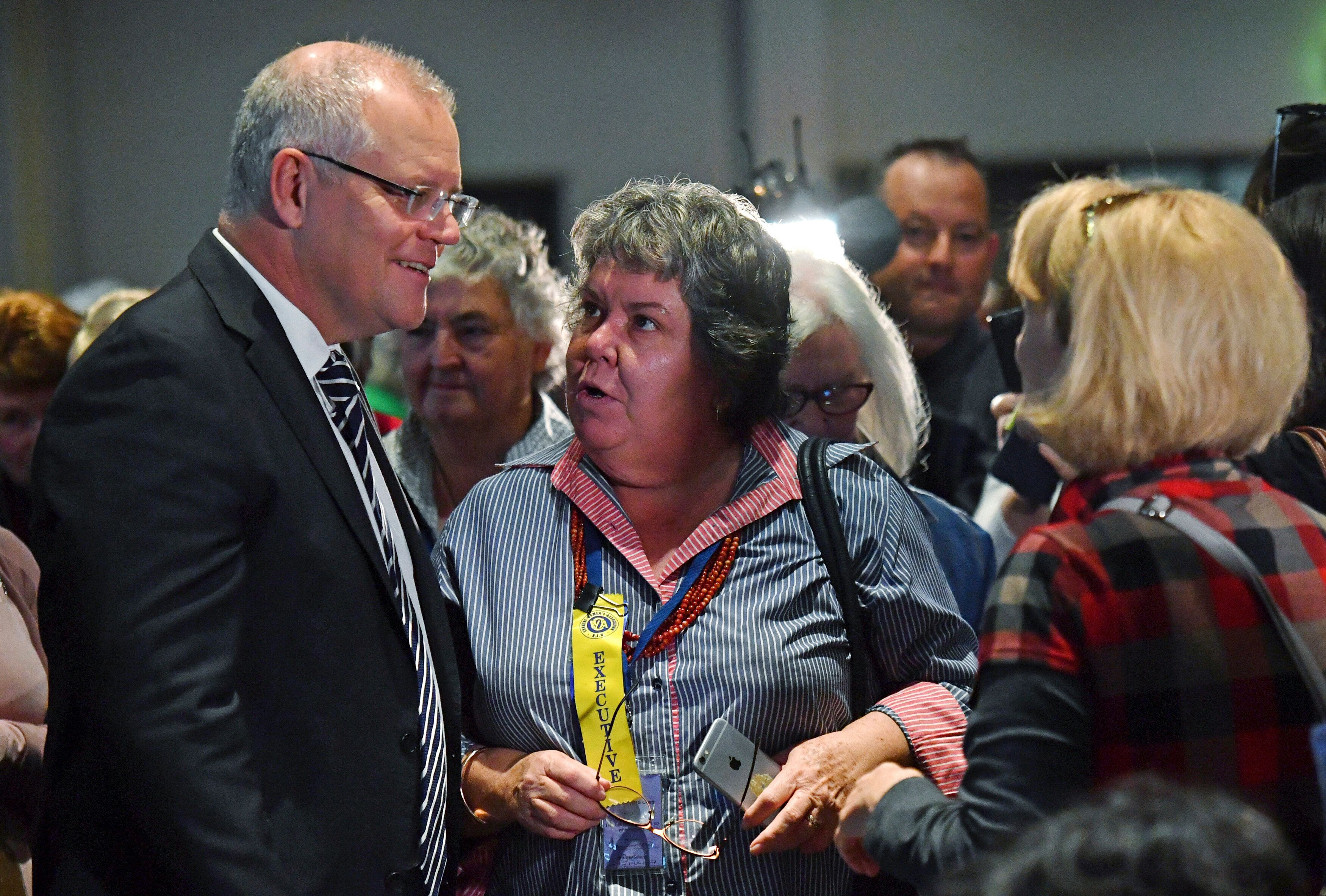 Australian Prime Minister Scott Morrison, left, talks with attendees at the Country Women's Association NSW annual conference in Albury, Tuesday, May 7, 2019. Morrison was was hit on the head with an egg and a woman was knocked off her feet during a protest at the event. (Mick Tsikas/AAP Image via AP)