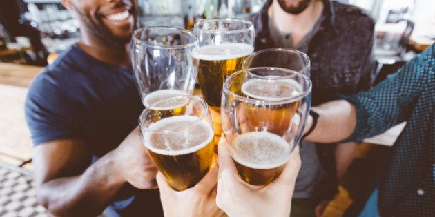 Multi ethnic group of friends toasting with beer glasses. High angle view, close up of hands. Unrecognizable people.