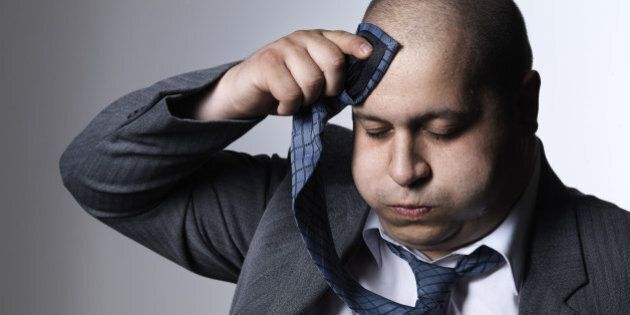 A hefty man in a suit wipes the sweat off his forehead with his tie. Photographed against a white background.