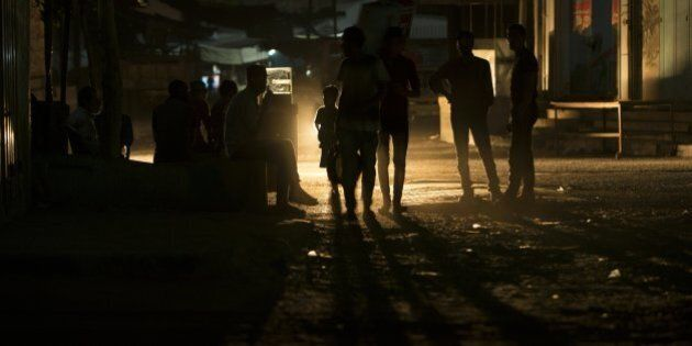 Palestinians walk on a street at the Al-Shati refugee camp in Gaza City during a power outage on June...