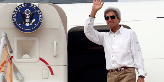 Secretary of State John Kerry waves as he boards his plane to depart Tan Son Nhat International Airport...