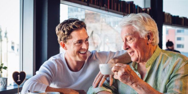Mature father and son enjoying a coffee together, the son looks proud of his dad and they are chatting happily together.