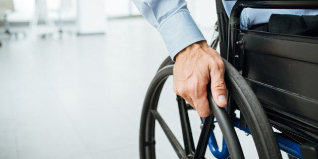 Businessman in wheelchair, hand on wheel close up, office interior on